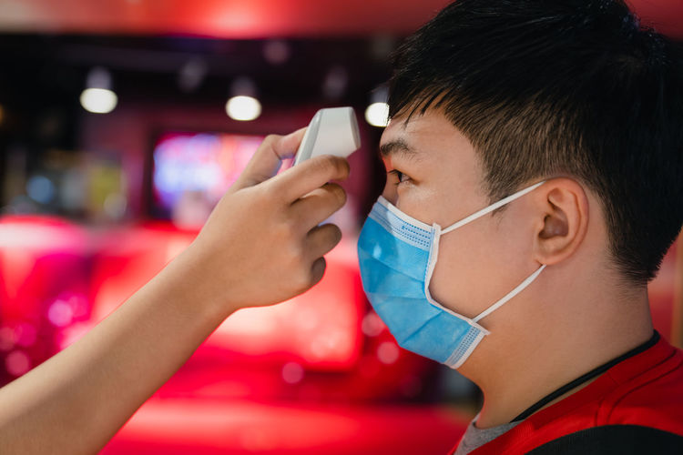 Cropped hand checking temperature of boy wearing flu mask
