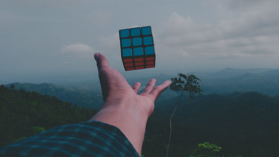 Cropped hand of woman reaching puzzle cube against sky