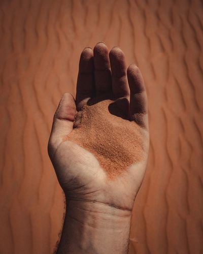 High angle view of human hand against sand
