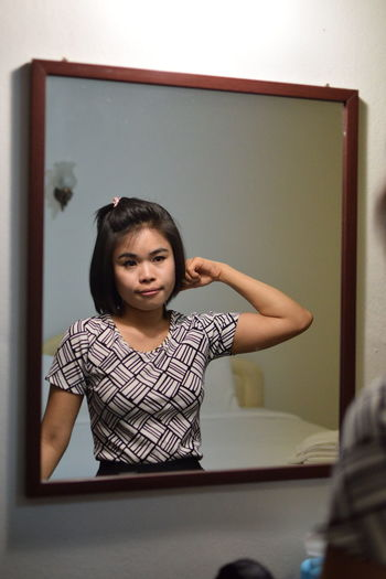 Young woman combing hair reflecting on mirror at home