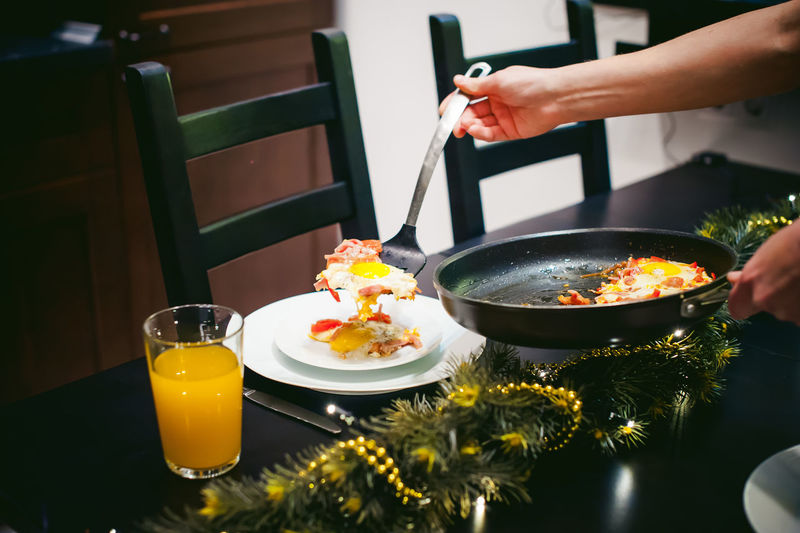 Midsection of woman serving food while standing by dining table at home