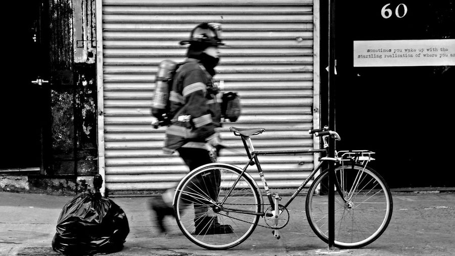 Blurred Motion Of Fireman Walking By Cycle On Sidewalk