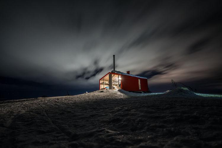 Lifeguard hut on beach by sea against sky at dusk