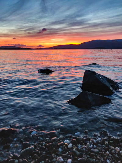 My first visit at Loch Lomond lake! Sky Sunset Water Sea Beauty In Nature Scenics - Nature Cloud - Sky Tranquility Beach Orange Color Land Nature Horizon Tranquil Scene Idyllic Solid Rock Horizon Over Water No People Outdoors Pebble Phone Photography Oneplus Scotland