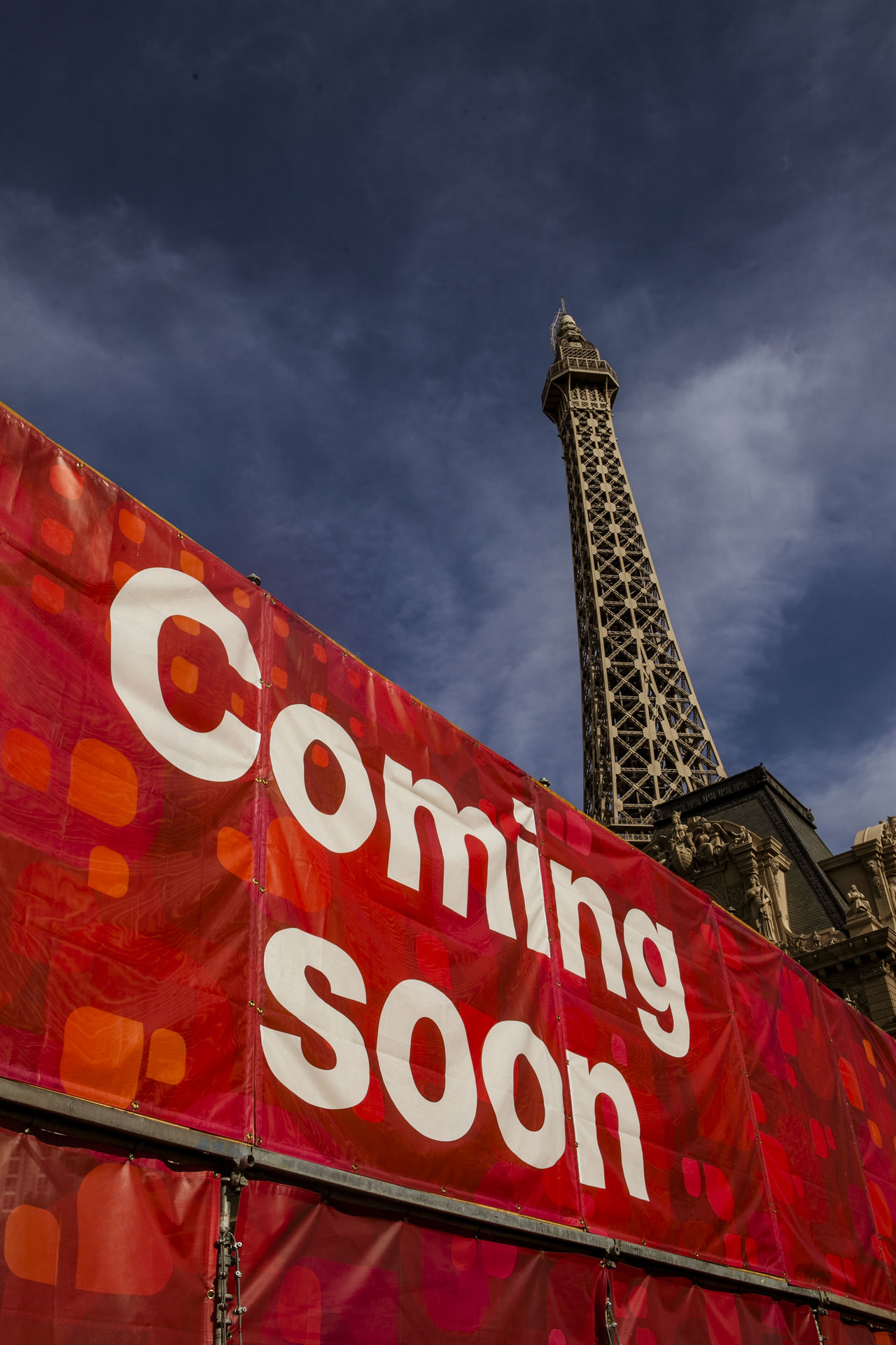 Low angle view of text on red canvas by paris las vegas hotel against sky