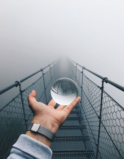 Cropped hand of man holding crystal ball on footbridge against fog