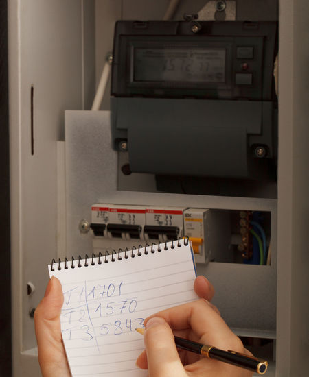 Cropped hand writing on diary against electric meter