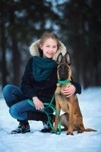 Portrait of teenage girl with dog in snow