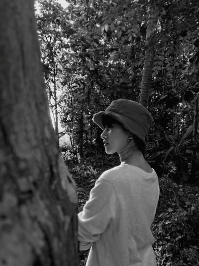 Thoughtful young woman standing at forest