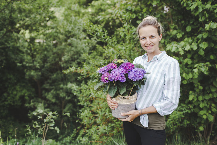 Young woman holding flower bouquet against plants