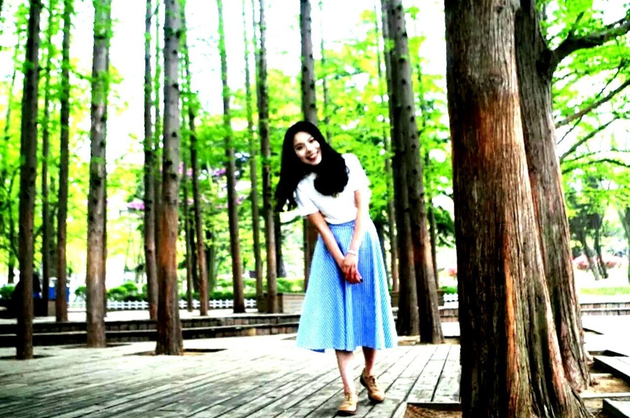 tree, dress, one person, standing, black hair, one woman only, young adult, adults only, long hair, looking at camera, beautiful woman, day, forest, only women, beauty, portrait, people, adult, outdoors, one young woman only, beautiful people, tree trunk, full length, nature, young women, evening gown