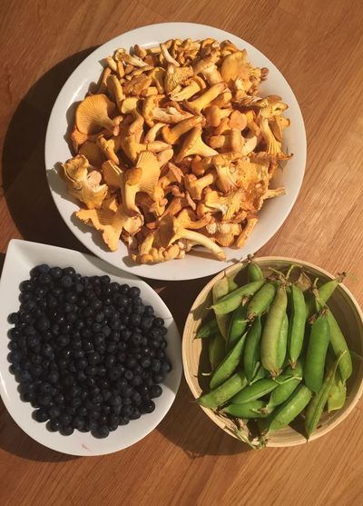 High angle view of green peas with mushrooms and blueberries in bowl