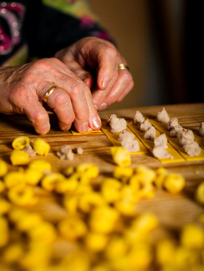 Tortellini homemade Modena Adult Close-up Egg Pasta Finger Food Food And Drink Freshness Hand Holding Human Hand Indoors  Italian Food Occupation Parma Ham Parmigiano Pasta Preparation  Selective Focus Senior Adult Skill  Tortellini  Women Wood - Material Working