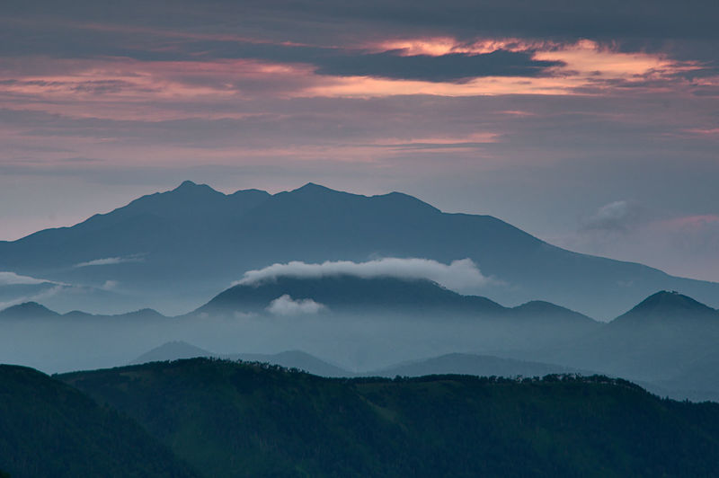 Scenic view of silhouette mountains against cloudy sky