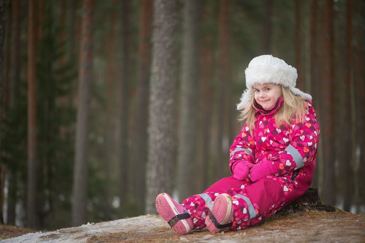 Portrait Of Smiling Girl In Warm Clothing Sitting By Trees In Forest During Winter