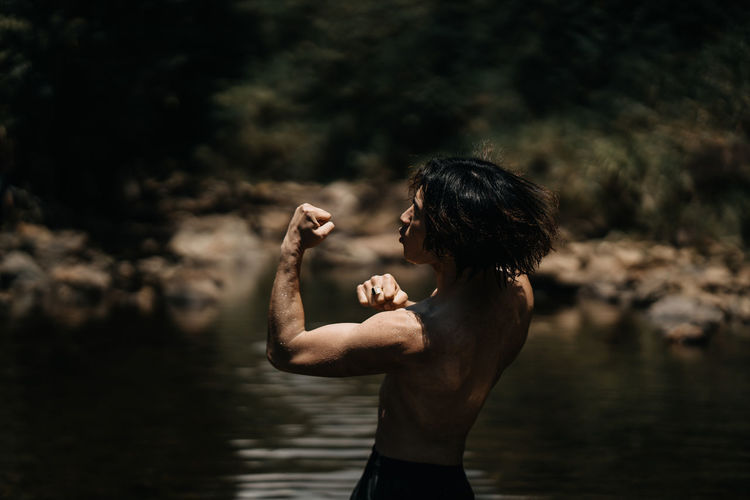 Side view of shirtless man standing by lake