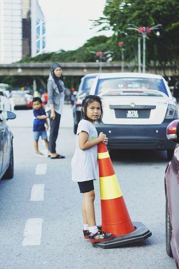 Rear view of siblings walking on road