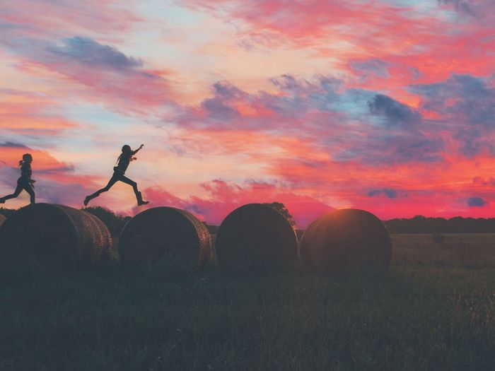 Silhouette Friends Running On Hay Bales Against Cloudy Sky At Sunset