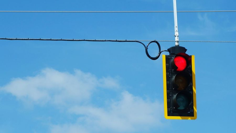 Low angle view of road signal against blue sky