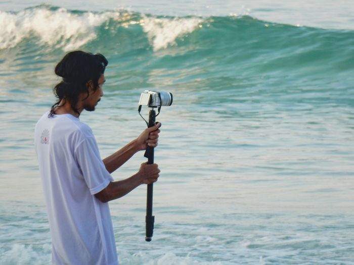 Young man photographing with camera on monopod while standing at seashore