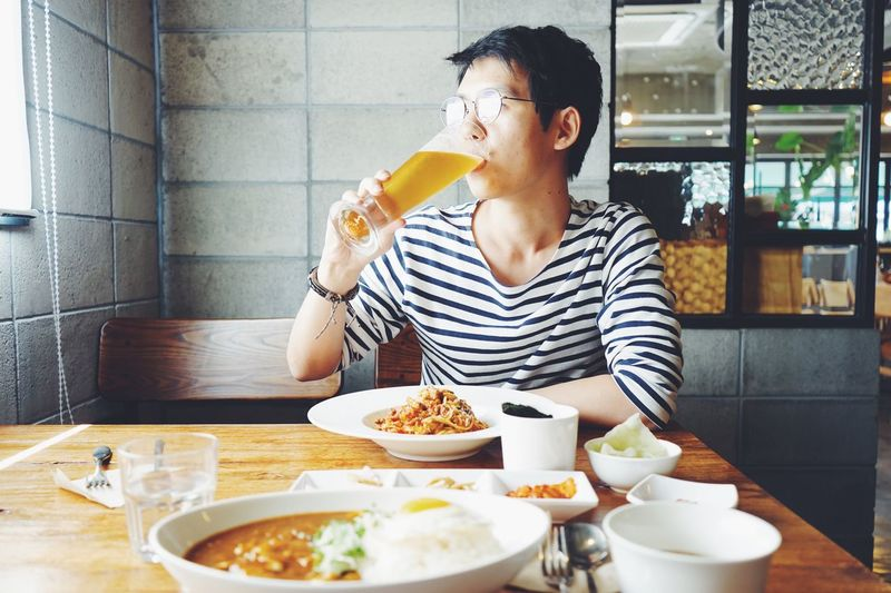 Man drinking beer while having lunch in restaurant