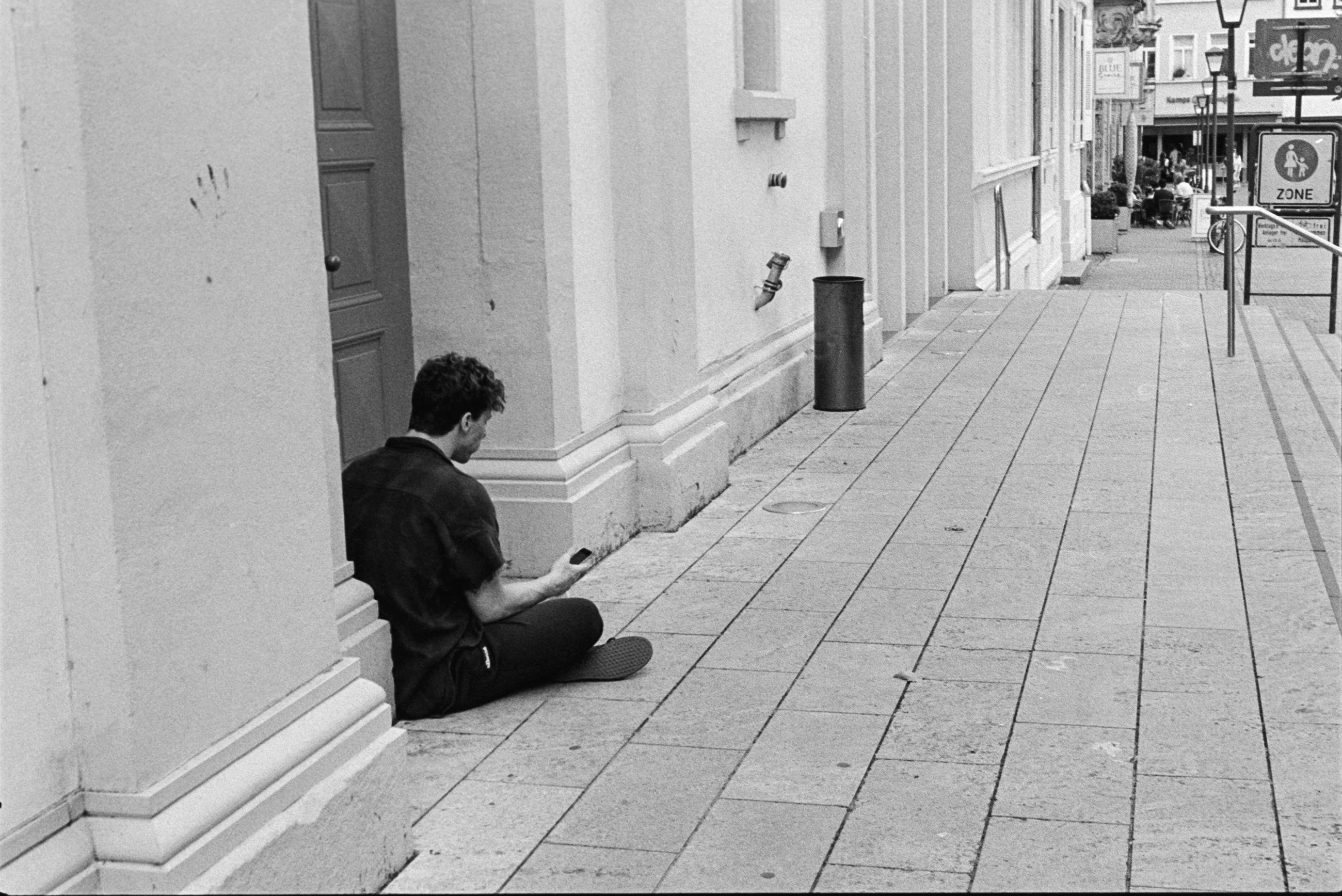 sitting, one person, men, full length, real people, architecture, building exterior, city, built structure, lifestyles, day, social issues, side view, leisure activity, footpath, casual clothing, relaxation, sidewalk, paving stone