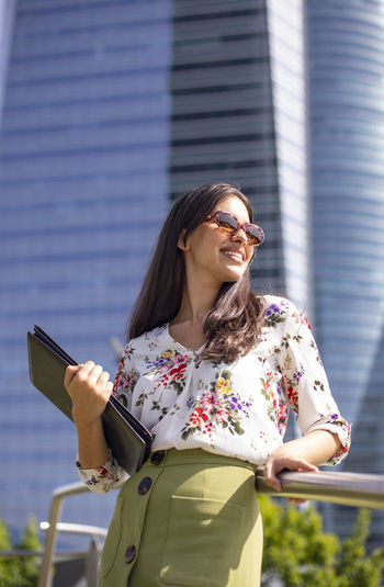 Young woman using phone while standing outdoors