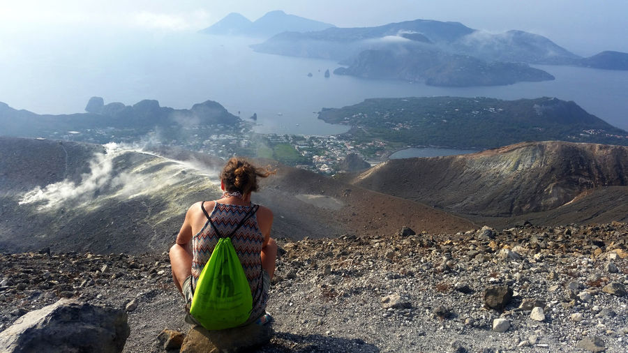Rear View Of Woman Sitting With Bag Against Mountains And Sea