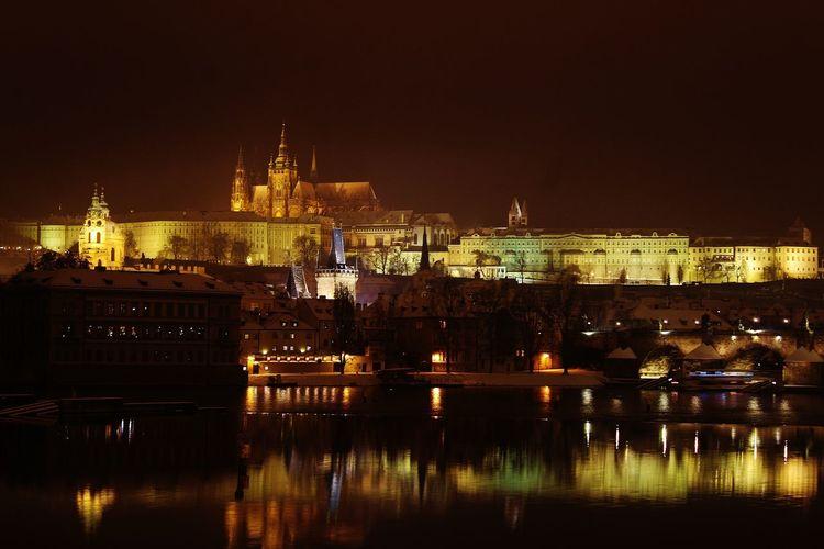 Illuminated prague castle by vltava river at night