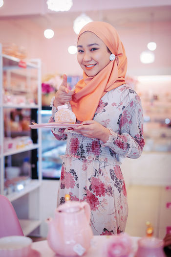 Portrait of a smiling young woman standing in store