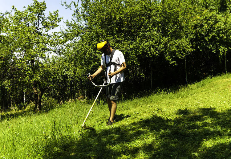 Full length of man cutting grass with weed trimmer
