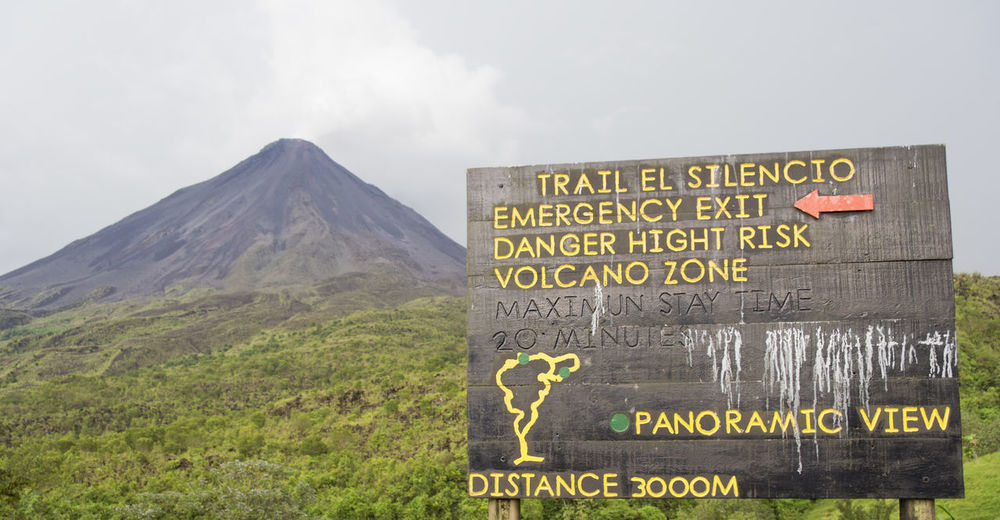 Information sign in front of Volcano Arenal in Costa Rica - La Fortuna, Alajuela province, Costa Rica Abandoned Active Volcano Alajuela Arenal Volcano Arenal Volcano National Park Costa Rica Extreme Terrain Forbidden Guidance Information Sign La Fortuna Landscape Mountain No People Signboard Smoke Text Travel Destinations Tropical Climate Volcanic Crater Volcanic Landscape Volcano Volcanoes Vulcano Warning Sign