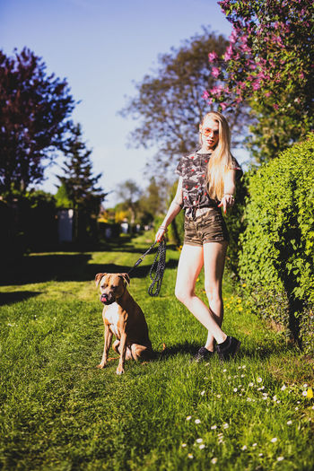 Young woman standing by dog on grassy field