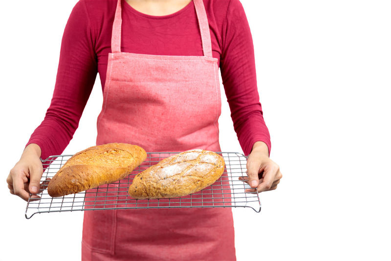 Midsection of woman holding food against white background