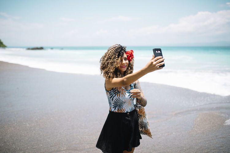 Woman taking selfie while standing at beach against sky
