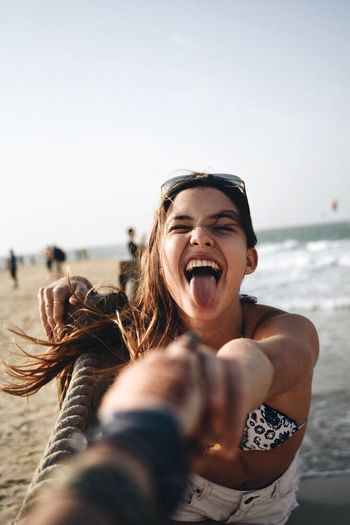 Portrait of young woman sticking out tongue on beach