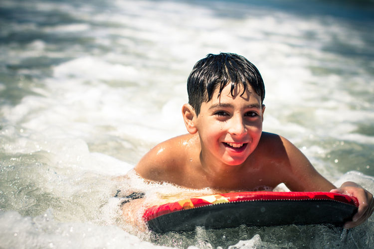 Portrait Of Boy Bodysurfing In Sea