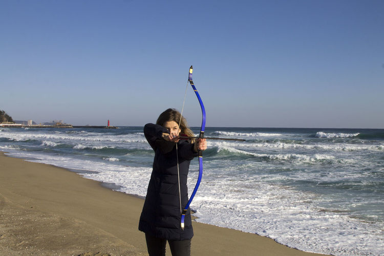 Female Archer Aiming While Standing Against Sea At Beach