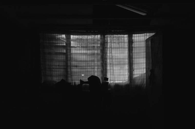 Silhouette man standing against window in building