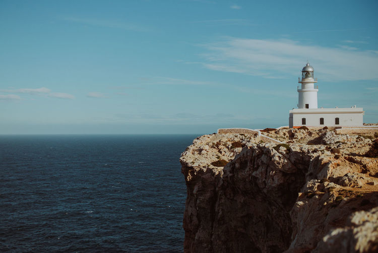 Lighthouse on cliff by sea against sky