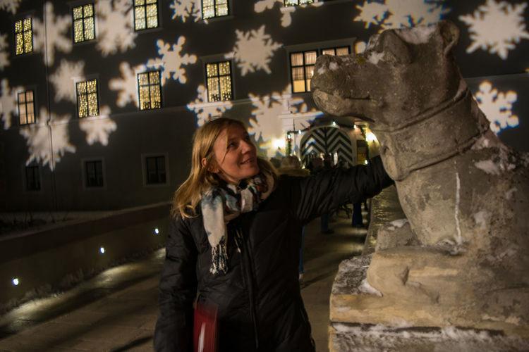 steinerner Wachhund mit bewunderndem Fan Young Woman Erleuchtete Fenster Schneeflocken Adventstimmung Bewundern Hund Aus Stein Adventmarkt  Brückenwächter City Warm Clothing Portrait Residential Structure