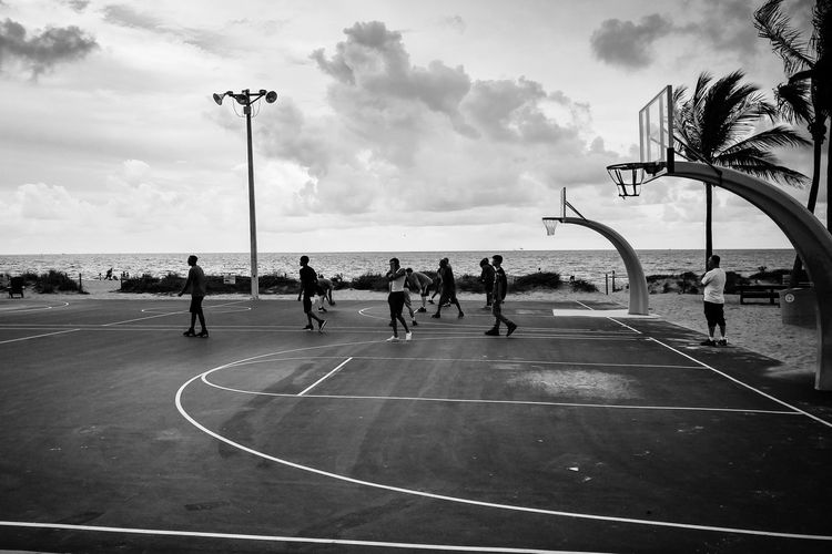 People playing basketball court against sky
