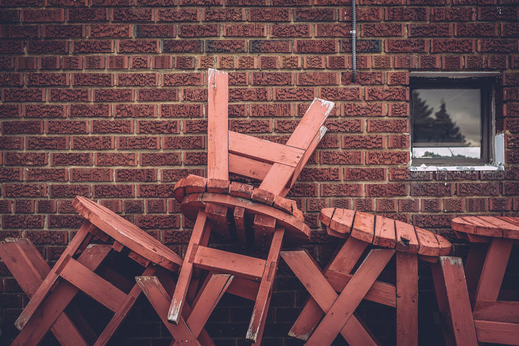 Stack of wooden tables against brick wall