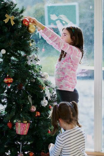 Full length of girl with christmas tree