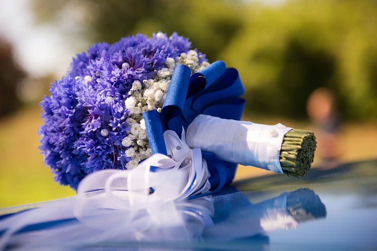 Close-up of purple bouquet on car bonnet
