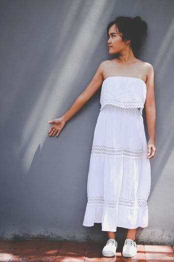 Beautiful Young Woman Wearing White Dress While Standing Against Wall