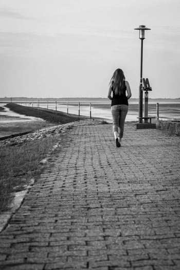 Rear view of woman walking on footpath leading towards beach