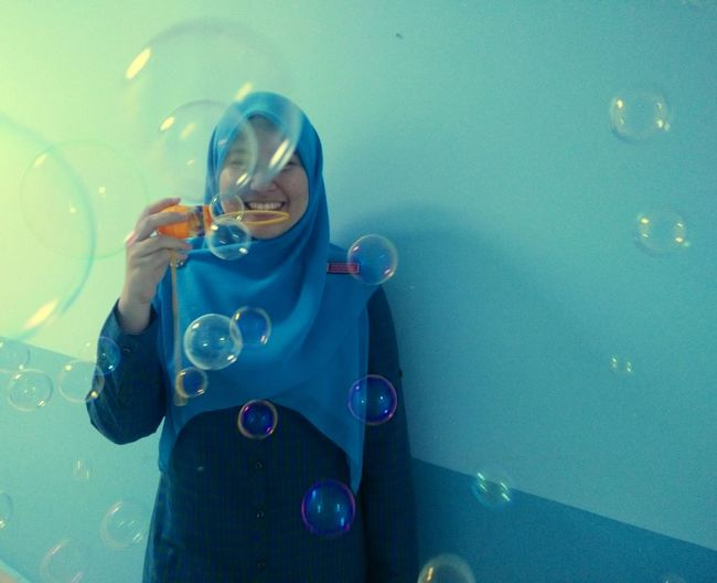 Happy woman blowing bubbles indoors
