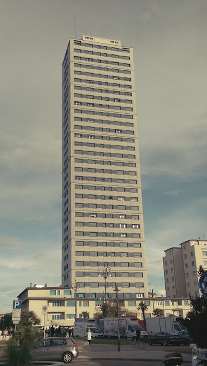 architecture, built structure, building exterior, car, tall - high, city, skyscraper, sky, land vehicle, cloud - sky, transportation, street, mode of transport, low angle view, city life, modern, day, outdoors, road, cityscape, no people