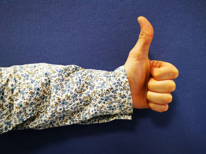Cropped hand showing thumbs up sign